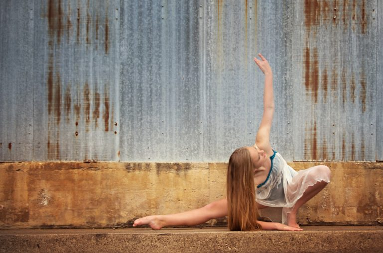 dance student posing in front of blue wall