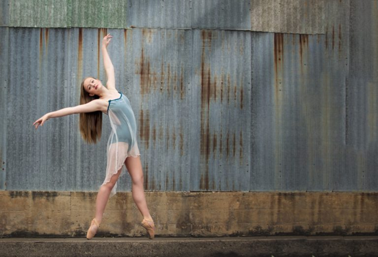Dancer en pointe in front of corrugated wall